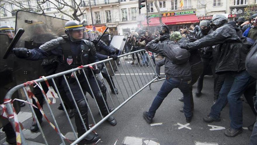 Manifestantes chocan con los policias durante la manifestación contra el COP21. / Efe