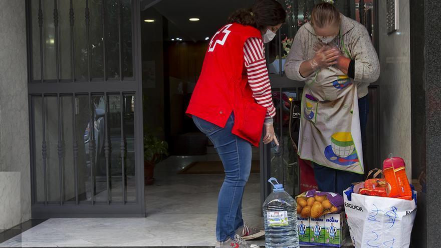 Una voluntaria de Cruz Roja lleva un lote de alimentación a una mujer víctima de violencia de género