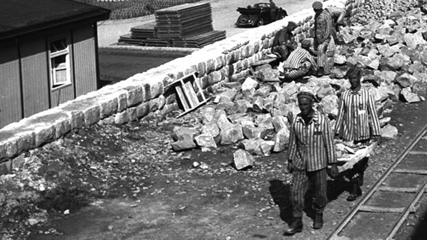 Prisioneros de Mauthausen transportan piedras para la construcción del campo