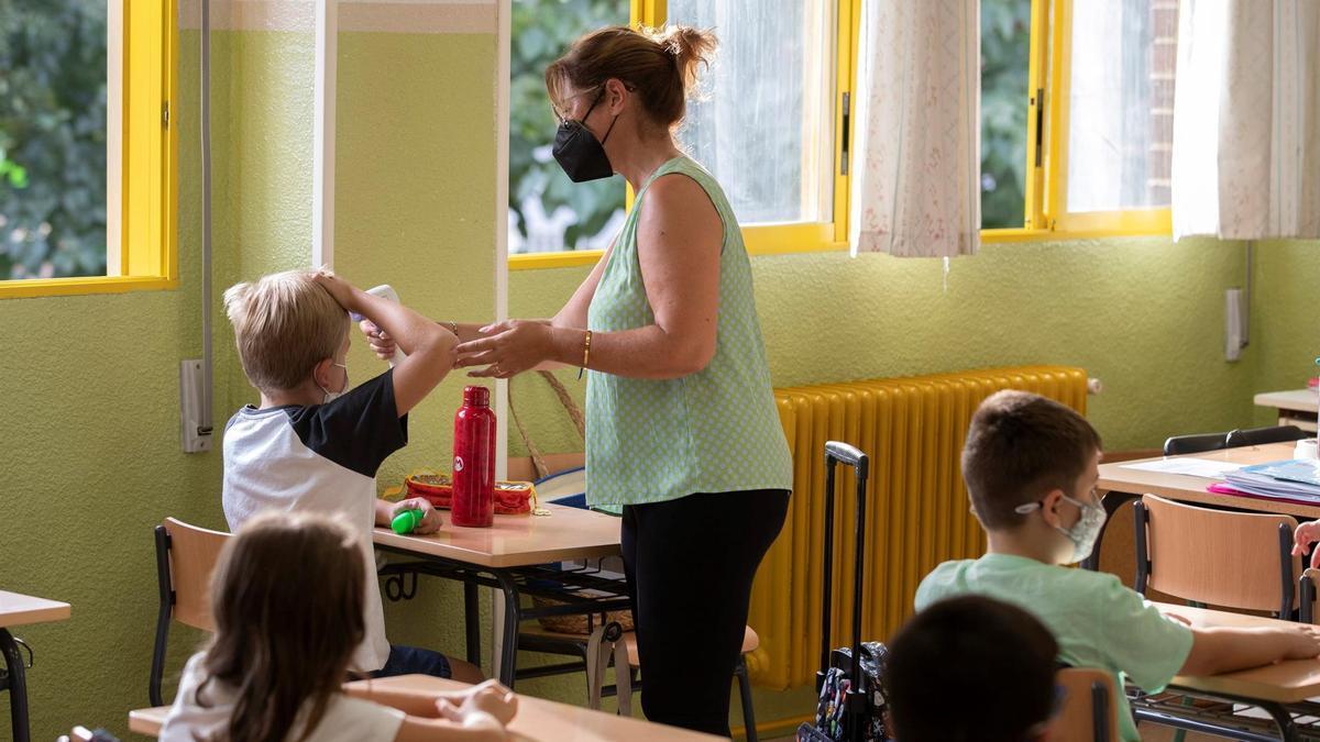 Una maestra del colegio público Federico de Arce de Murcia toma la temperatura a un alumno, este martes en el que arranca el curso escolar para los alumnos de Primaria en la comunidad murciana.