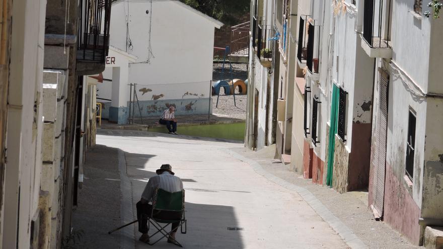 Dos vecinos de Chalamera aprovechan la sombra antes de la hora de comer. Al fondo, la escuela.