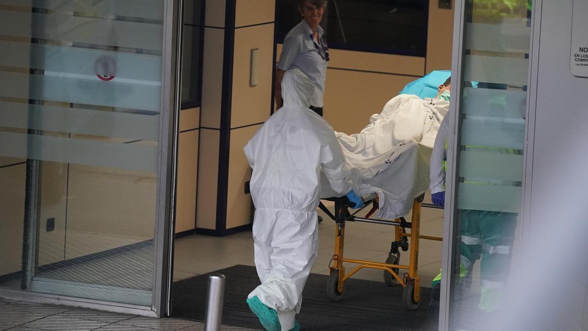 Un sanitario protegido con un traje y guantes de látex, empuja una camilla con una persona sobre ella en el Hospital Universitario Cruces,