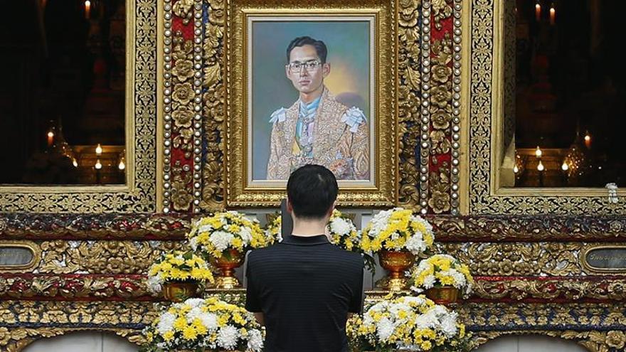 Un hombre reza ante una fotografía del rey Bhumibol Adulyadej en el templo Wat Bowonniwet en Bangkok, Tailandia, el 18 de octubre de 2016, cinco días después de que falleciera el monarca, el jefe del Estado más longevo. EFE