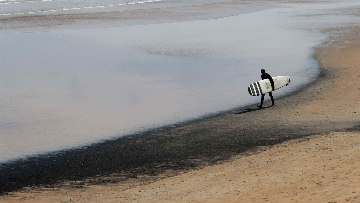 Un surfista transporta su tabla en la playa de San Lorenzo de Gijón, este lunes.
