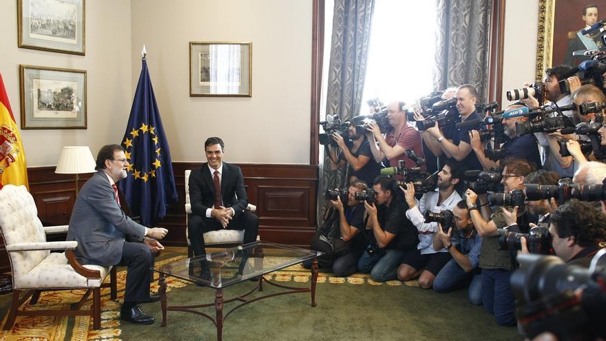 Rajoy y Sánchez posan sonrientes y se estrechan la mano, en una imagen muy diferente a la de febrero
