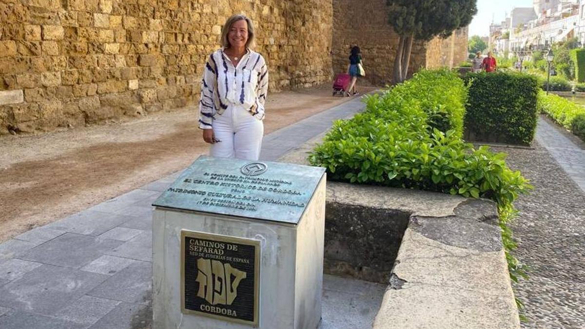 La delegada de Turismo, Isabel Albás, junto a la placa.