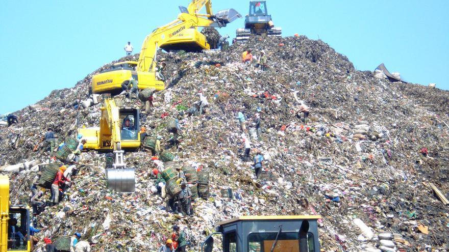 Imagen del vertedero Bantar Gebang con varios recolectores de basura peinando la montaña de desechos.