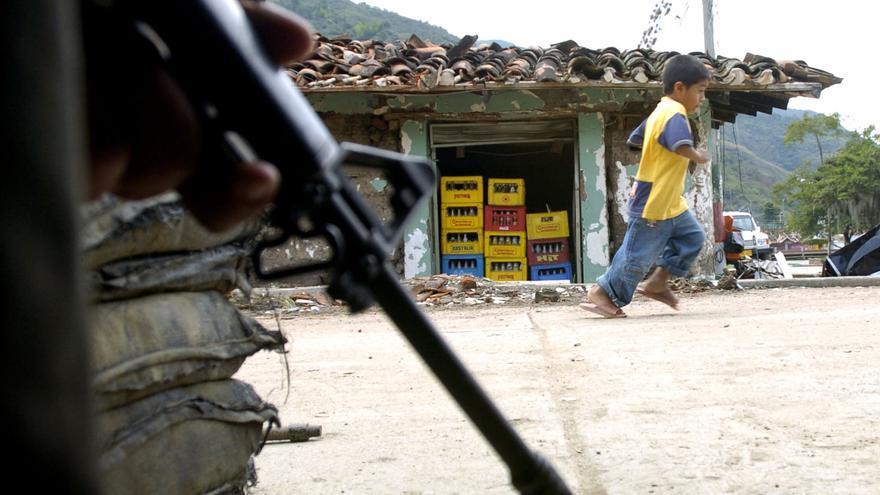 Un niño pasa por delante de un soldado en Toribio, Colombia / AP Photo/Zoe Selsky