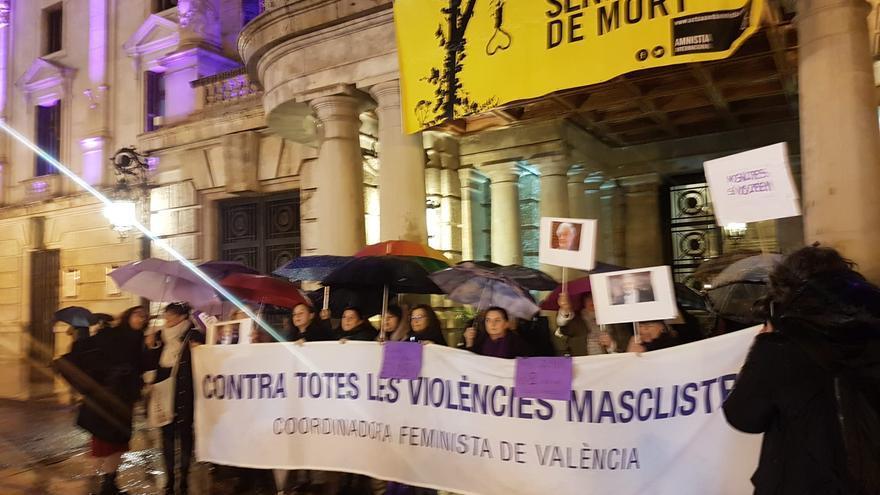 Medio centenar de mujeres protesta bajo la lluvia por la actuación de Plácido Domingo en Valencia.
