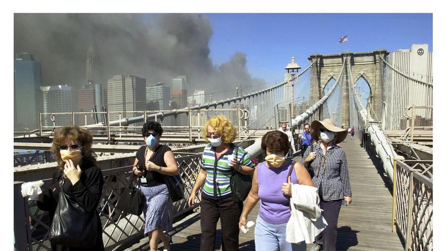 Mujeres con máscaras contra el polvo huyen por el puente de Brooklyn de Manhattan a Brooklyn, tras el derrumbe de las dos torres del World Trade Center Martes, 11 de septiembre de 2001 en Nueva York