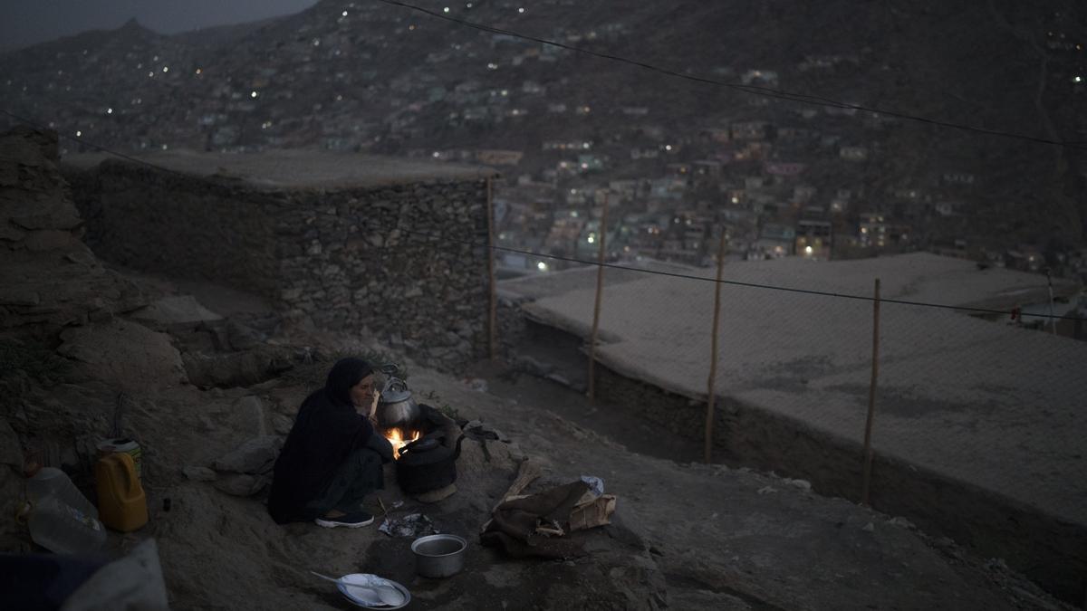 Una mujer cocina la cena fuera de su casa en Kabul.