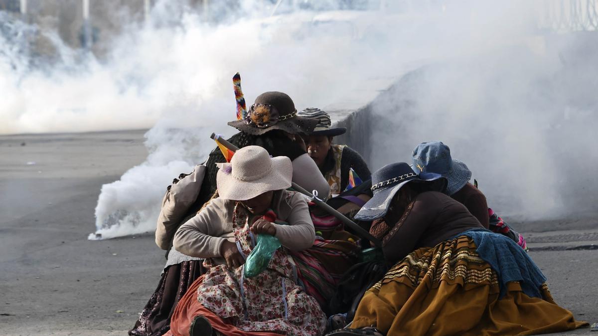 Mujeres indígenas bolivianas se protegen del gas lacrimógeno durante una protesta contra el gobierno interino en La Paz el 15 de noviembre de 2019.
