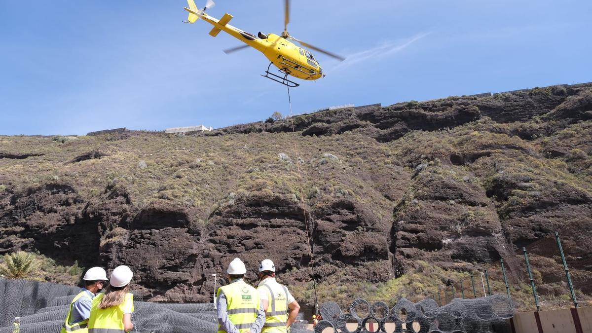 Helicóptero que participa en la instalación de los pilares de las mallas de protección para mejorar la seguridad del Puerto de Tazacorte.