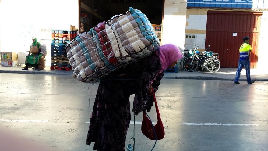 Una mujer carga un fardo en el polígono de El Tarajal