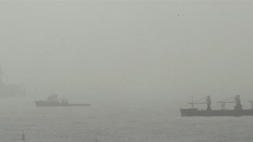 Dos barcos y una plataforma petrolífera fondeados en la bahía del puerto de Las Palmas se desdibujan entre la calima.