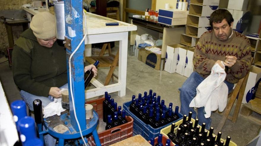Dos socios de l'Olivera colocan manualmente etiquetas a las botellas de vino Foto: L'Olivera