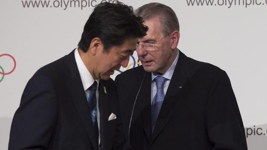 El presidente del COI, Jacques Rogge, habla con el primer ministro japonés, Shinzo Abe, durante la ceremonia de elección de la sede olímpica en 2013 en Buenos Aires.