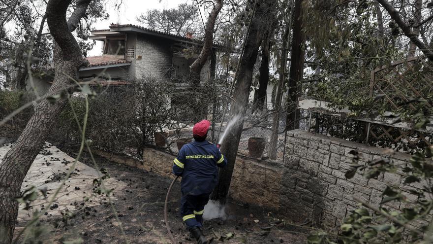 Un bombero apaga el fuego en el exterior de una casa incendiada en la localidad de Kineta, al oeste de Atenas.