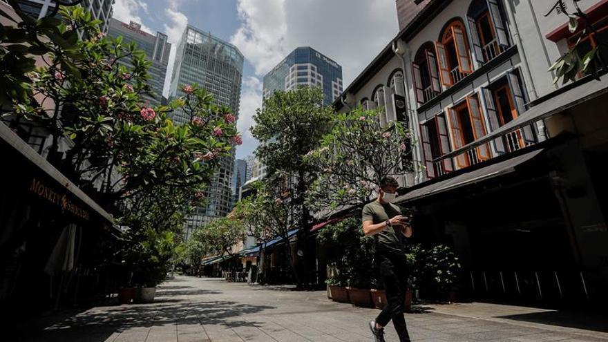 Un hombre protegido con una mascarilla pasa por una zona de tiendas en Singapur, el 14 de abril de 2020.