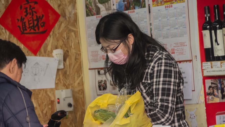 Una mujer atienda con mascarilla a los clientes de su tienda.