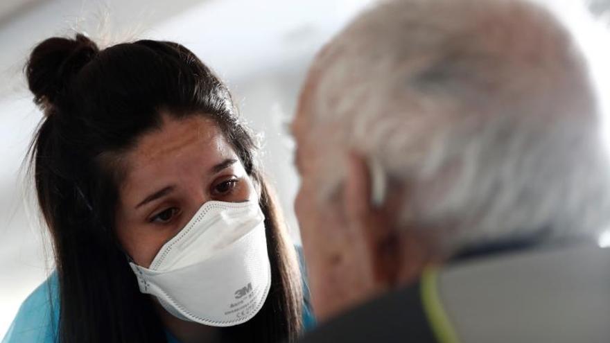 Una cuidadora atiende a uno de los ancianos alojados en una residencia de Madrid