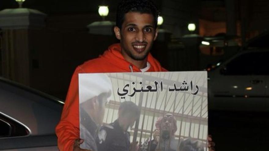 El periodista kuwaití Ayyad al-Harbi, sosteniendo un cartel con la foto de un compañero detenido. Imagen tomada de su cuenta de Twitter