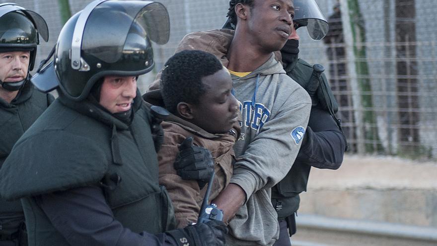 Dos agentes antidisturbios acompañan a varios inmigrantes uno de ellos visiblemente herido y sin fuerzas/Blasco de Avellaneda