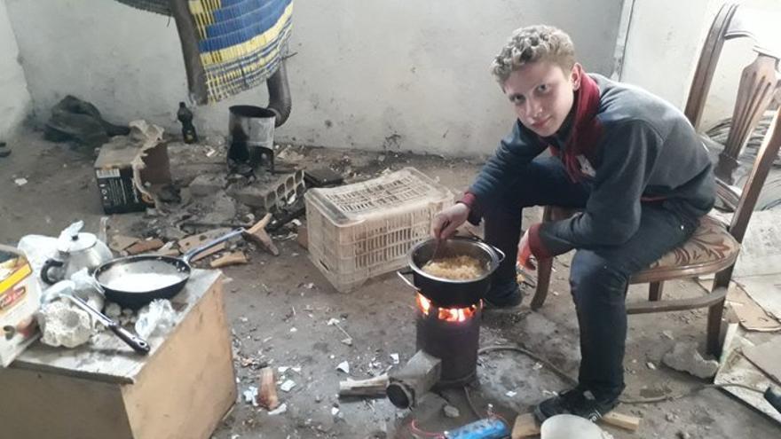 Muhammad Najem come de un hornillo de gas rodeado de escombros.