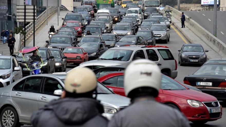 Dos policías montan guardia mientras decenas de manifestantes bloquean con sus coches el tráfico en protesta contra el Gobierno.