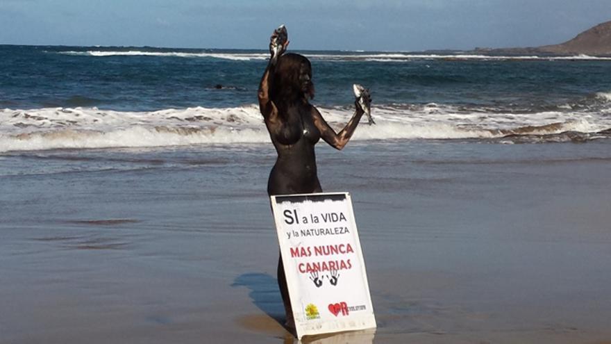 La activista Jil Love realiza una 'performance' contra las prospecciones petrolíferas en la playa de Las Canteras de Las Palmas de Gran Canaria.