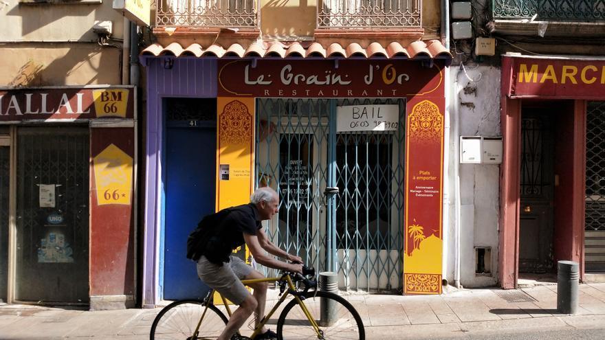 Un ciclista sube la calle Fusterie de Perpiñan en dirección a la plaza Rigaud