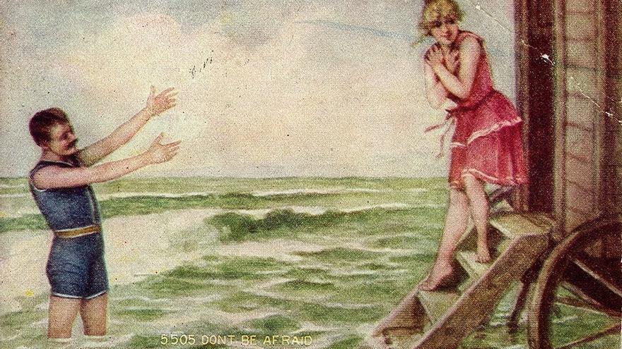 Una postal de 1912 con un hombre y una mujer en traje de baño junto a un 'carro de baño'.