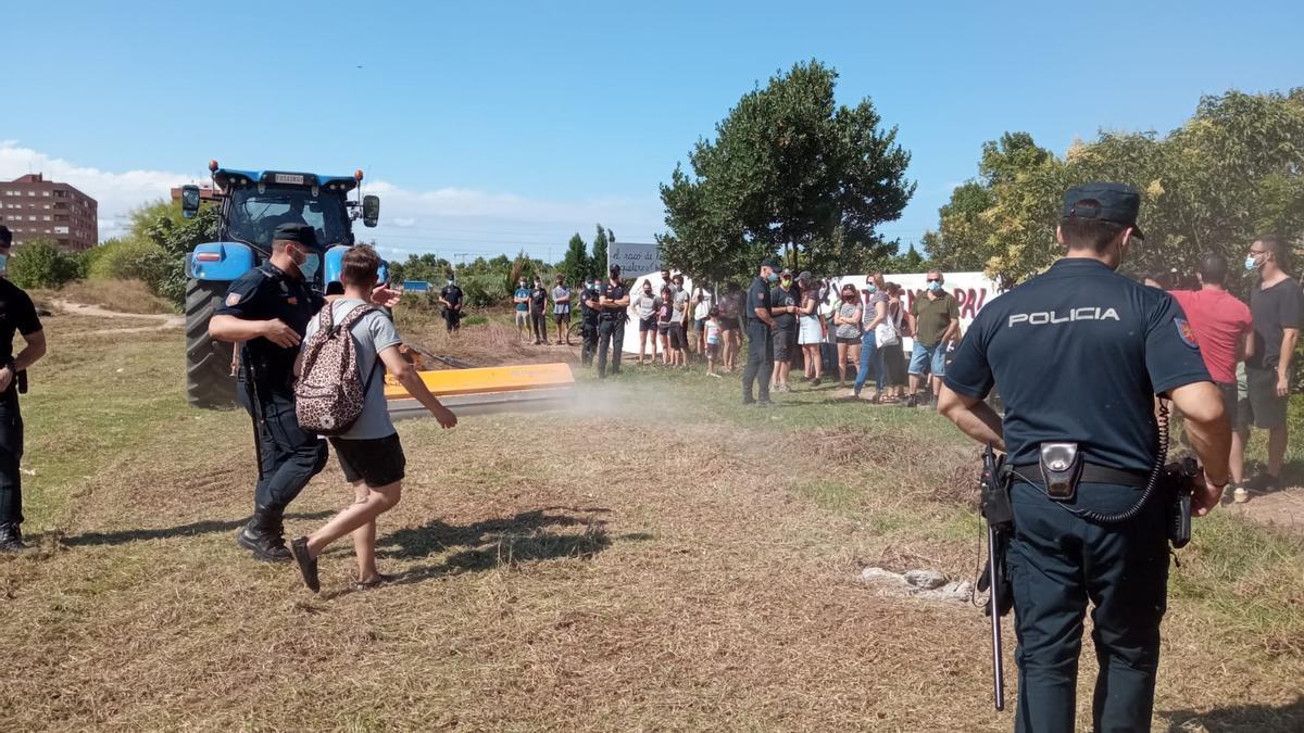 Agentes de la Policia Nacional protegen las máquinas excavadoras en el solar de Benimaclet.