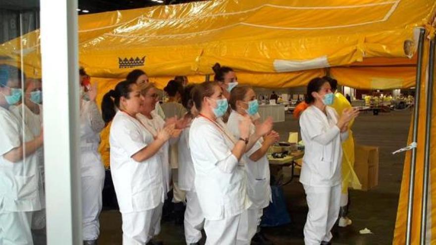 Personal sanitario aplaude este lunes la primera alta a uno de los pacientes atendidos por coronavirus en el  hospital provisional instalado en la Feria de Madrid (Ifema)