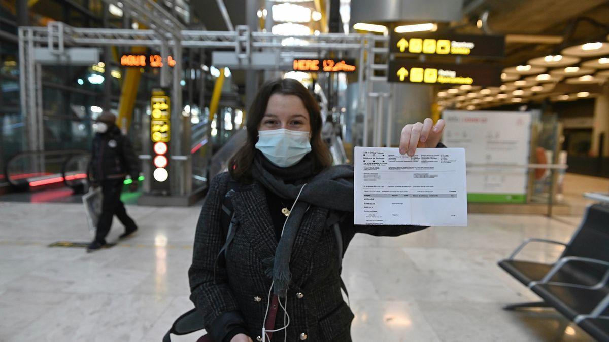 Una joven muestra el resultado de su PCR