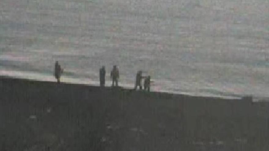 Un agente lleva a uno de los inmigrantes que llegó a territorio español a empujones. Cuando llega donde está el resto del grupo, esta persona se intenta levantar y vuelve a caer de rodillas. Captura de uno de los vídeos de las cámaras de seguridad.