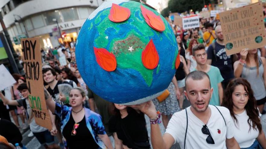 Un joven lleva un globo terrestre en llamas durante una manifestación por la emergencia climática.