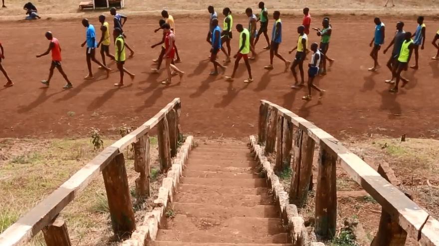 Un amplio grupo de atletas, donde se entrelazan mujeresy hombres, caminando por la pista de entrenamiento tras una sesión