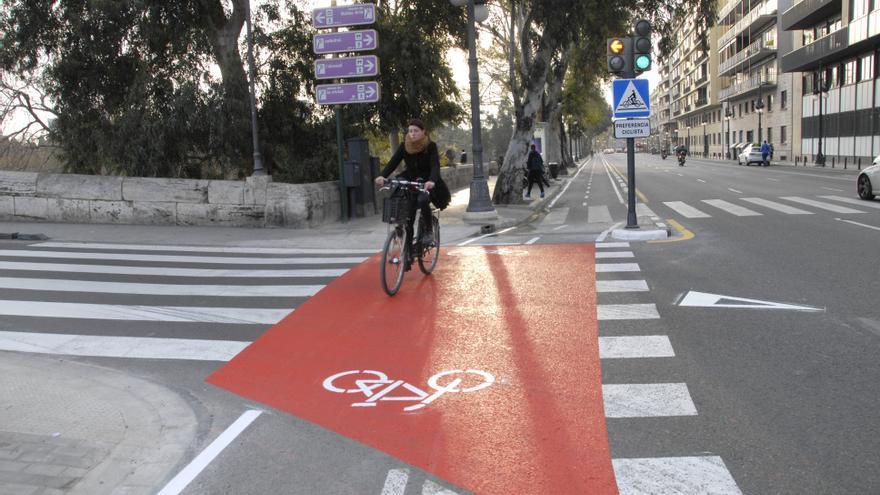Una ciclista cirlcula por un cruce del anillo ciclista
