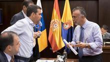 El vicepresidente primero del Cabildo de Gran Canaria, Ángel Victor Torres (d), charla con el consejero de la oposición, Lucas Bravo de Laguna (i), durante un Pleno del Cabildo de Gran Canaria.