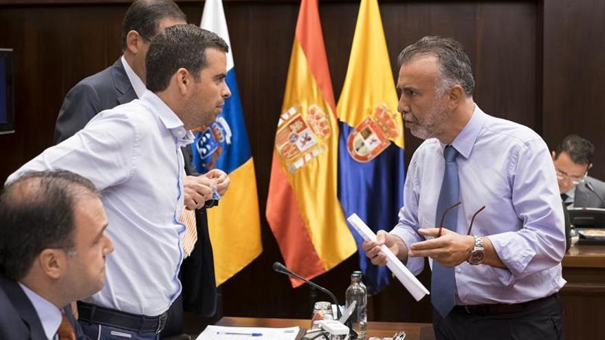 El vicepresidente primero del Cabildo de Gran Canaria, Ángel Victor Torres (d), charla con el consejero de la oposición, Lucas Bravo de Laguna (i), momentos antes del inicio del Pleno del Cabildo de Gran Canaria