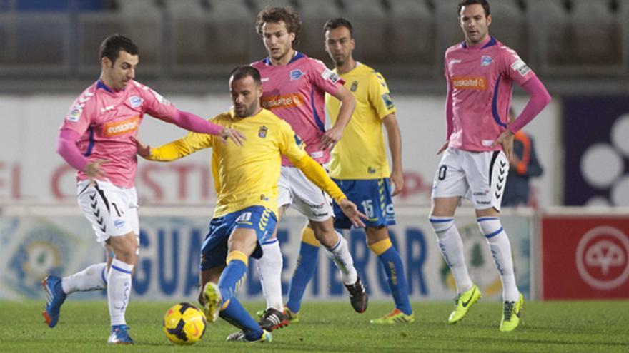 Apoño conduce el balón ante la mirada de varios contrarios durante el partido que disputaron la UD Las Palmas y el Deportivo Alavés en el Estadio de Gran Canaria. udlaspalmas.es