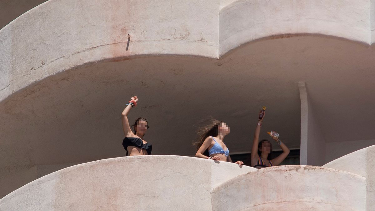 Tres jóvenes que se encuentran en aislamiento tras tener relación directa o indirecta con el brote por covid de un viaje de estudios en Mallorca, bailan en la terraza de una habitación del hotel.
