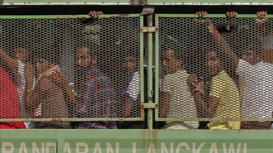 """Migrantes bangladesíes y rohingya, un grupo étnico musulmán de Birmania, son trasladados en camiones a una base naval, antes de ser transferidos al muelle de Kuala Kedah en la embarcación de la Armada """"KD Mahawangsa"""", desde Langkawi (Malasia). EFE"""