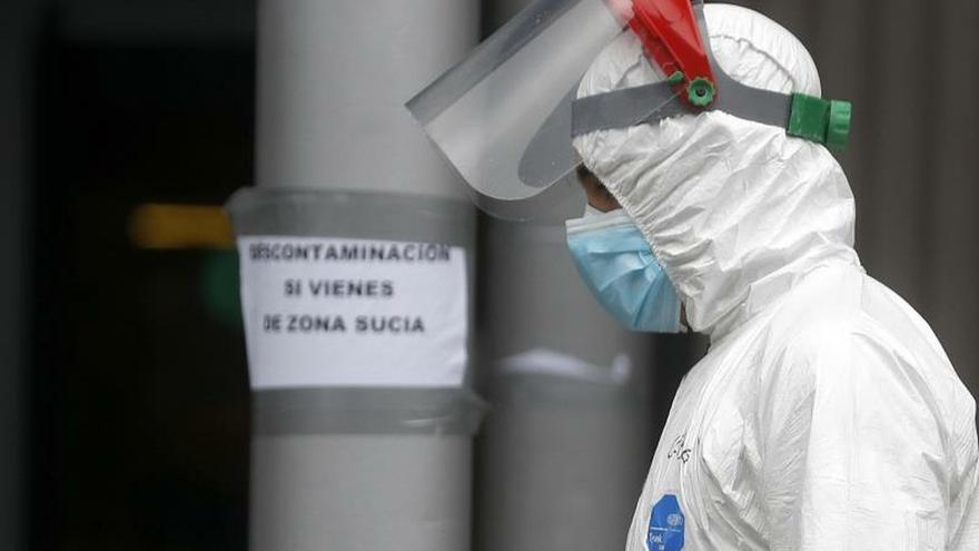 Un trabajador, con el traje de protección, cruza una zona común, situada entre pabellones, en el centro de exposiciones Ifema