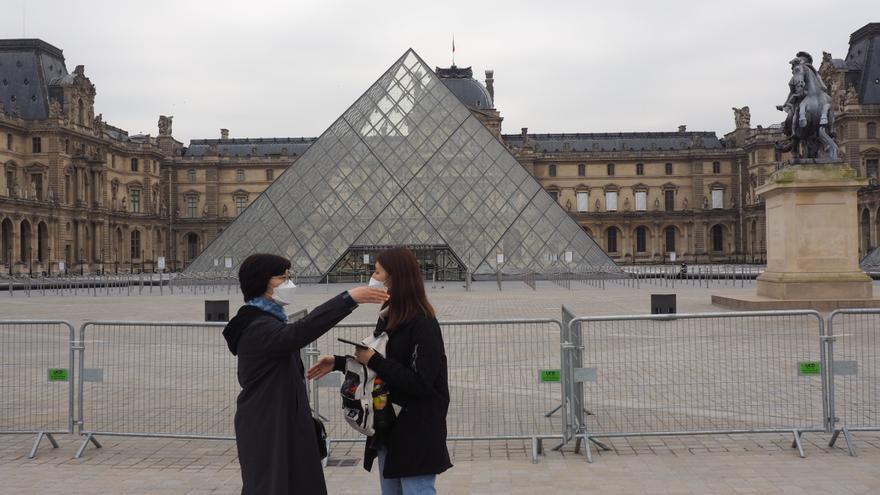 Turistas durante el estado de alarma en Francia a las puertas del museo del Louvre, cerrado por el brote de coronavirus