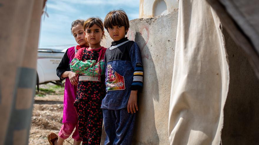 Tres de las hijas indocumentadas de Nada de pie fuera de su tienda de campaña en un campamento de desplazados cerca de Mosul