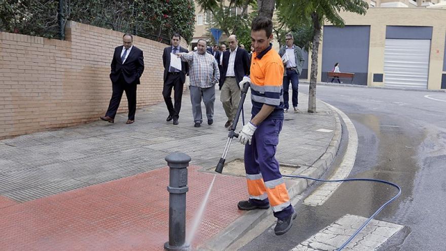 Un operario limpiando mientras al fondo camina el alcalde de Alicante, Gabriel Echévarri