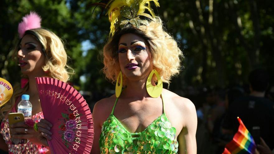 Una mujer aplaca el calor con un abanico en el desfile del Orgullo