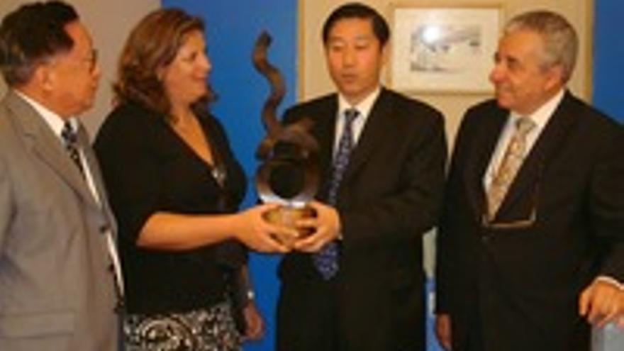 Rita Martín entrega al millonario chino Zheng una escultura de Andrés Allí. A la derecha, Olarte.